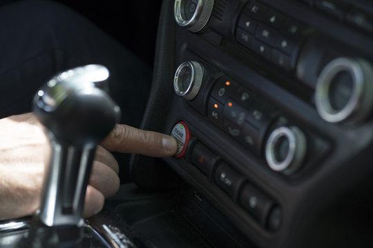 Crop man starting car with button