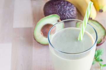 Healthy smoothie with avocado, banana, milk and honey on wooden background, horizontal, copy space, closeup