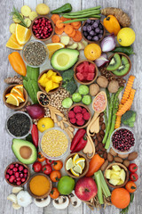 Health food concept with fruit, vegetables, herbs, spice, nuts, seeds, grain and pulses. Super foods high in antioxidants, anthocyanins, smart carbohydrates, fibre, vitamins and minerals.
