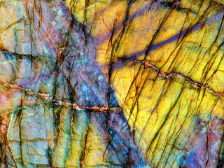 Amazing colorful texture of iridescence Labradorite Mineral gemstone background macro close-up. Beautiful reflective shiny Crystal