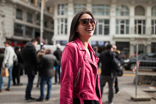 Stylish woman in pink jacket on street