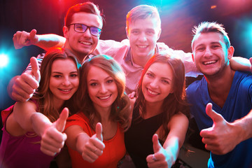 Young people showing OK sign in the night club
