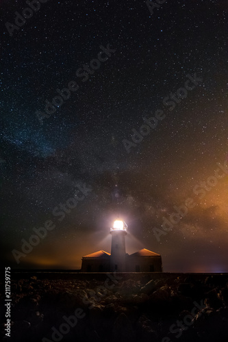 Lighthouse shining in the night of stars