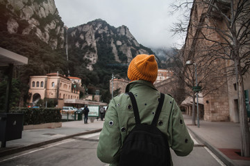 Young female traveler with hat and backpack standing in Monserrat square with tower and basilica Back view.Discovering Europe