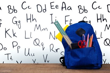 Schoolbag on wooden table