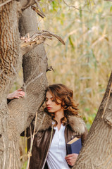 Young woman with curly hair dressed in brown trousers and leather jacket is standing with blue book near autumn tree with fallen leaves. Autumn. Education at university, school. Examinations of poet.