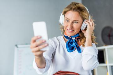 attractive businesswoman in headphones taking selfie with smartphone in office