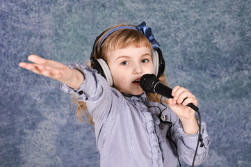 Beautiful little girl with microphone at home singing