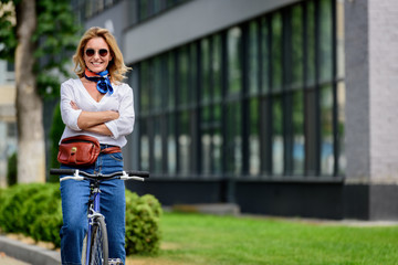 attractive woman sitting on bike with crossed arms on street