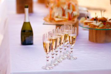 on a white table a bottle of champagne and 7 glasses, as well as food