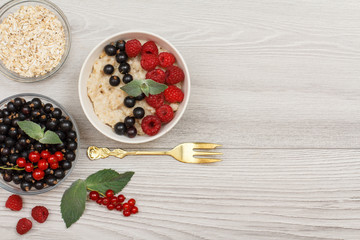 Oatmeal porridge in porcelain bowl with currant berries and raspberries, decorated with mint leaves
