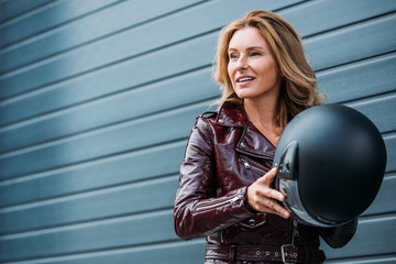 attractive woman in leather jacket holding motorcycle helmet on street and looking away