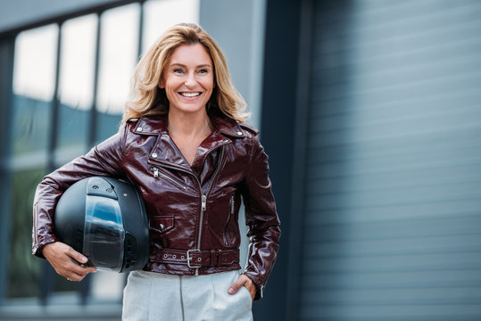 smiling woman in leather jacket holding motorcycle helmet on street and looking away