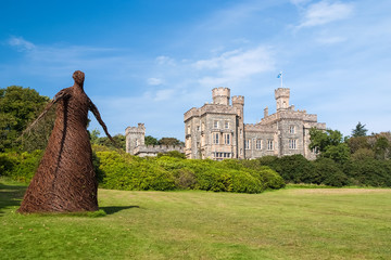 Keuken foto achterwand Kasteel Wicker woman statue and castle in Stornoway, United Kingdom. Willow sculpture on green grounds of Lews Castle estate. Architecture and design. Landmark and attraction. Summer vacation and wanderlust