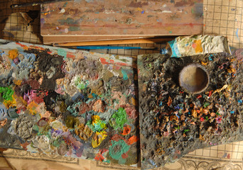mixed art paint on the board, brush and tube. the view from the top. concept: artistic and creative chaos