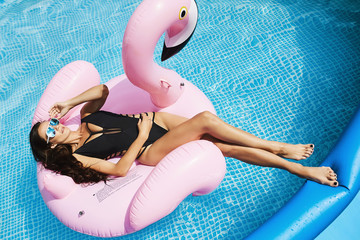 Hot and fashionable brunette, fitness model girl with perfect sexy body in stylish black bikini and glamorous sunglasses, tanning on an inflatable pink flamingo and posing at the swimming pool
