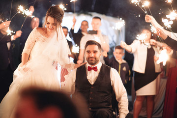Crowd with Bengal fires greets bride and groom on the wheelchair in the night