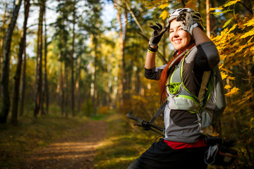 Photo of girl in helmet on bicycle in autumn forest