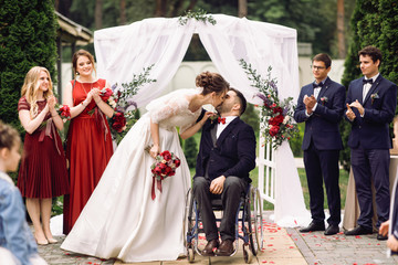Bride and groom on the wheelchair kiss before wedding altar after the ceremony