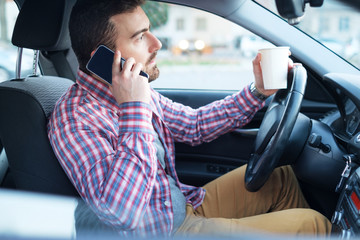 Man driving his car and using mobile phone