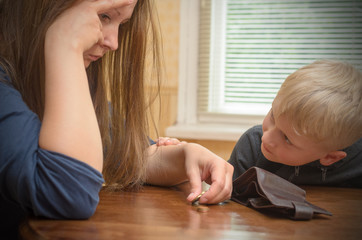 A sad woman at the table thinks the last coins. Empty wallet - boy son calms mother.