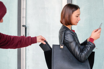 Thief picking the wallet from the bag of a careless girl