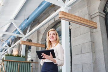 Positive beautiful blonde - the manager of large financial company holds tablet and looks somewhere during meeting in a large beautiful office.