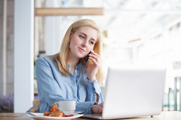 Pretty young woman outsourcing employee of large company working remotely sitting at table in cafe talking on smartphone with laptop using high-speed Internet.
