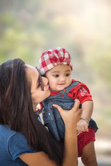 Portrait of Indian/Asian mother Kissing her cute little daughter in the park, Family outdoor lifestyle.