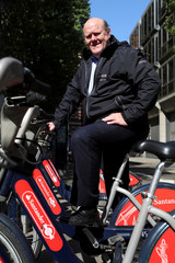 Rupert Soames, CEO of Serco Group Plc poses for a photograph on a London rental bike outside their offices in London
