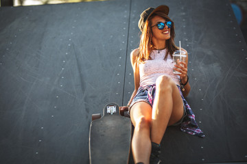 Teen female skater sitting on ramp at the skate park .