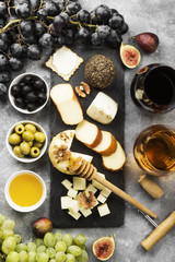 Snacks with wine - various types of cheeses, figs, nuts, honey, grapes on a gray background. Top view. Food background