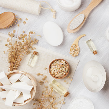 Rustic white homemade cosmetics set of natural products for body care and bath accessories with spikelets on white wood board, top view.