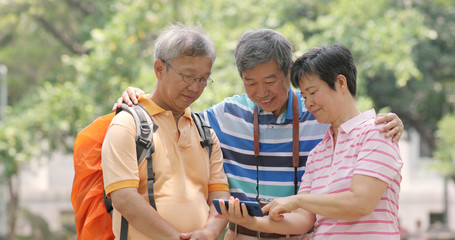 Senior old friends go travel together with backpack, cellphone and camera