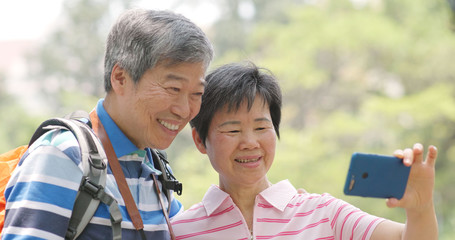 Asian old couple go travel and use of mobile phone at countryside