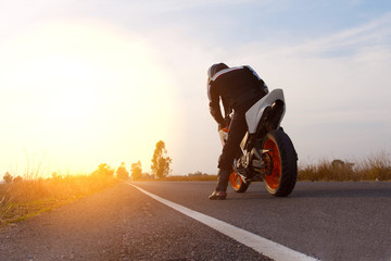 Motorbike riding on road with sunset