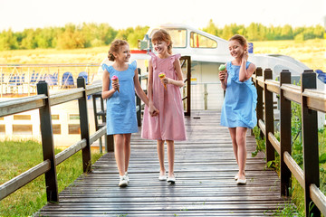 Fashion 3 three girlfriend 9-11 years. Lady kids, elegant striped dresses in marine style. Little girls cool,summer clothes outdoors.Designer children's collection. Friendship,smile,resting together.