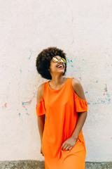 Cheerful African-American woman near concrete wall
