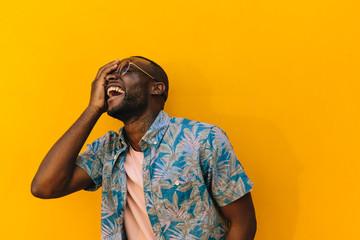 Cheerful black man portrait covering an eye