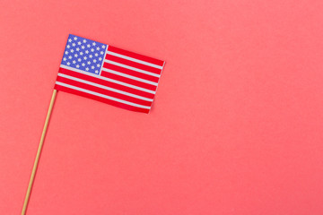 Small paper american flag on wooden stick on bright background