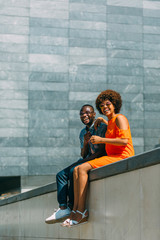 Laughing black couple sitting on border