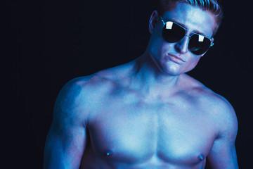 Male sunglasses & body concept. Portrait of a handsome muscular male model in trendy sunglasses posing over black background. Studio shot