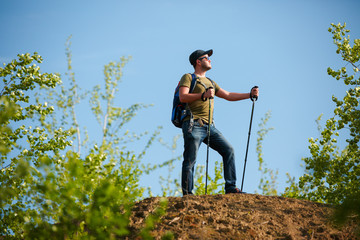Picture of man with backpack and walking sticks on hill