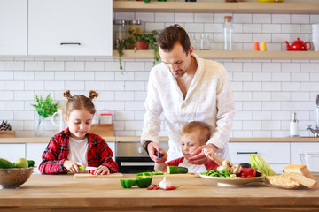 Photo of father with daughter and son cooking at table