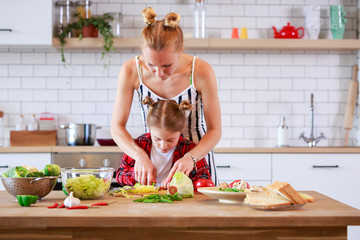 Photo of young mother with her daughter cooking food in kitchen