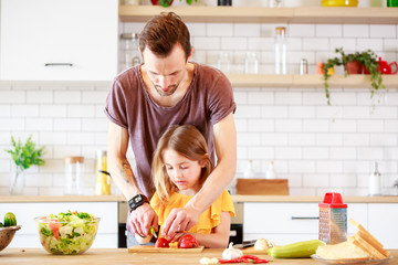 Photo of father with little daughter cooking lunch