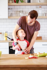 Photo of father with son cooking vegetables