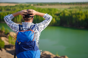 Picture from back of young tourist with backpack with hands behind head against background of mountain landscape, lake