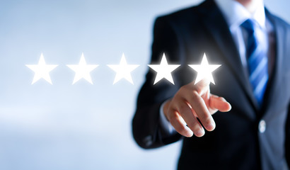 Businessman pointing five star to increase. Customer feedback and experience concept.