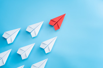 Leadership concept with red paper plane leading among white on blue background Wall mural